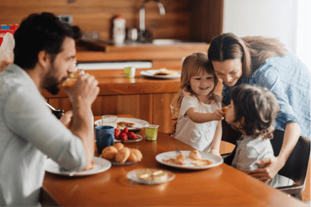 mom, dad, and two children having breakfast