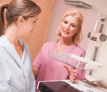 female doctor helping a female patient with mammogram machine