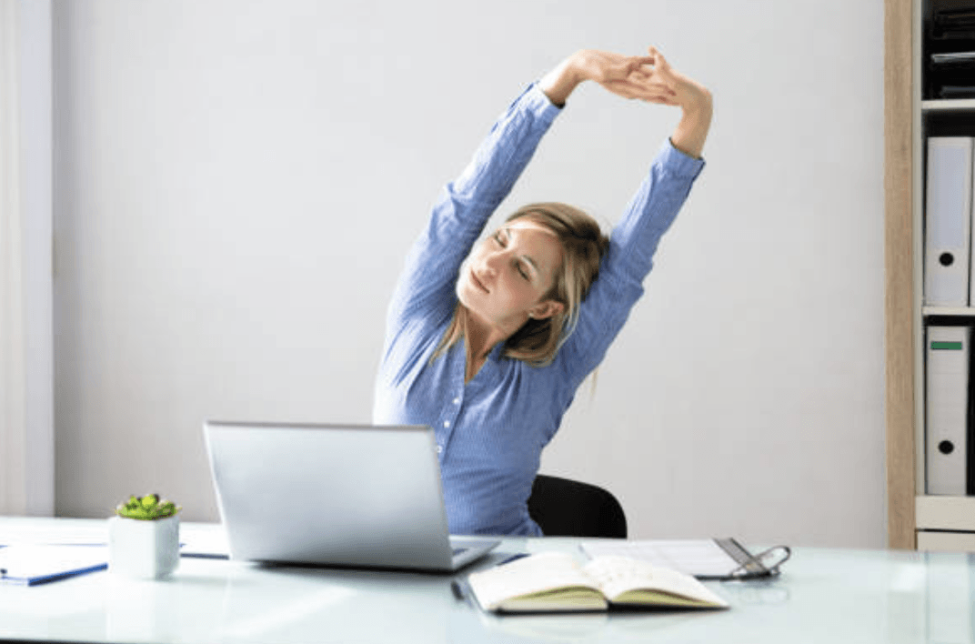 business woman stretching at her desk