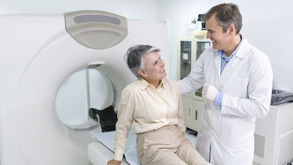 doctor talking to an older woman sitting on an mri machine